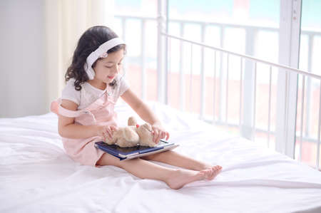 A cute Asian girl is using a tablet for fun playing games and learning  in the room