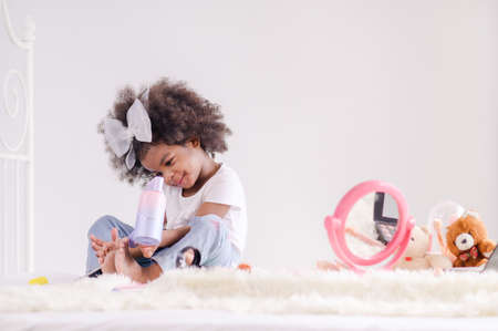 The cute little African girl happily uses an electric hair dryer in her bedroom Фото со стока