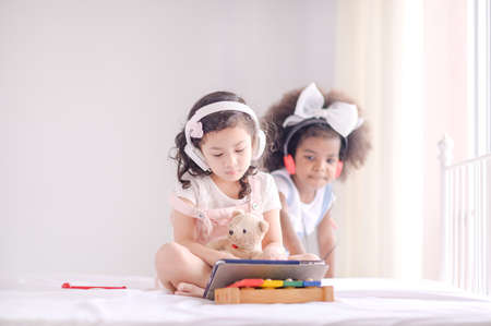 A cute Asian girl and an African kid friend are using a tablet to play games and have fun learning in the room