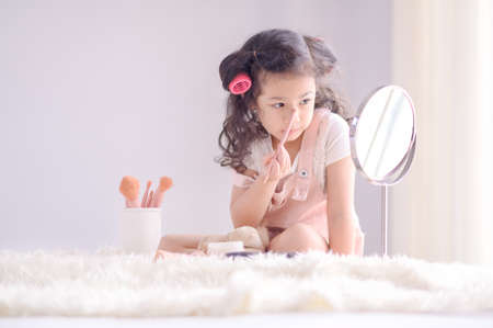 A cute little Asian girl is happily applying makeup brushes with powder in her bedroom