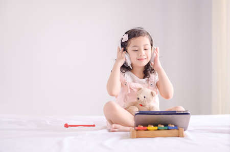 A cute Asian girl is happily using a tablet to listen to music and learning in bedroom Фото со стока