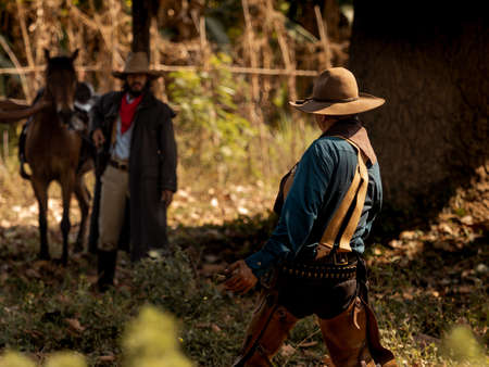 The senior cowboy stands preparing for a gunfight against opponents in the outlawed western lands