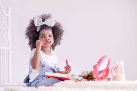 A cute African girl looks in the mirror and happily plays lipstick on her lips in her bedroom Фото со стока