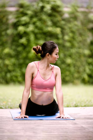Asian women meditation and stretching relax their muscles by doing yoga in the garden Фото со стока