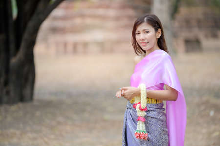 Attractive Thai women in traditional Thai dress hold fresh flower garlands for entering a temple based on the Songkran festival tradition in Thailand