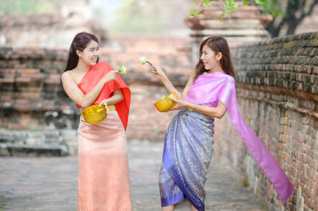 Attractive Thai lady in traditional Thai dress holding lotus flowers playing with friends On the Thai Songkran Festival