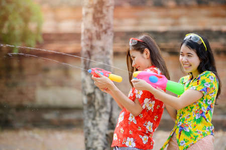 Beautiful Asian women hold plastic water guns at an ancient temple during Songkran, the most beautiful and fun water festival in Thailand
