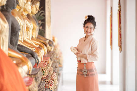 Attractive Thai woman in an ancient Thai dress holds a garland of fresh flowers paying homage to Buddha to make a wish on the traditional Songkran festival in Thailand