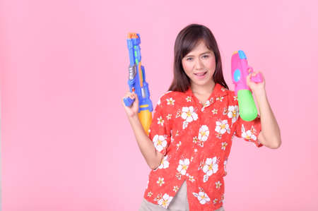 A beautiful Asian woman shows a gesture while holding a plastic water gun during the Songkran festival, Which is the most beautiful and fun festival in Thailand
