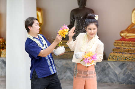 Young Thai men and women in traditional Thai dress hold flowers splashing water for fun at the Songkran water festival Фото со стока