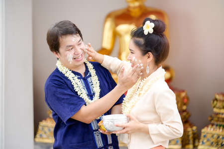 Thai men and women in Thai costumes use water-soluble powder to paint their cheeks with joy in celebrating the Songkran water festival