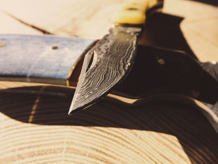 Damascus steel knife on wooden background