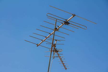 building feature: A television antenna on a house rooftop.