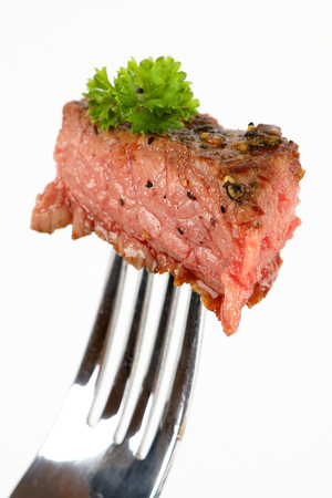 Medium grilled rumpsteak on a fork with white background Stock Photo