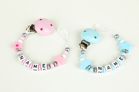 Two pacifier chains in blue and pink with white background