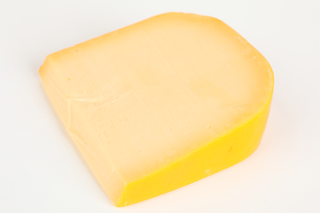 a piece of a youbng gouda with white background