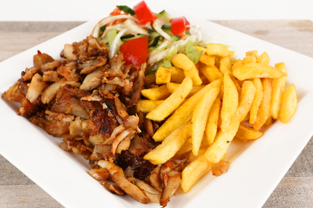 Chicken doner on a plate with fries and salad 스톡 콘텐츠