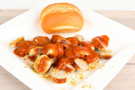 sliced sausage with curry sauce and a roll Stok Fotoğraf - 97429192