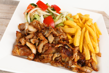 Chicken doner on a plate with fries and salad Stok Fotoğraf