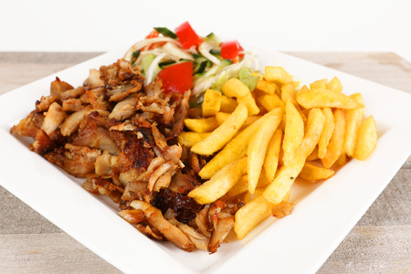 Chicken doner on a plate with fries and salad 版權商用圖片
