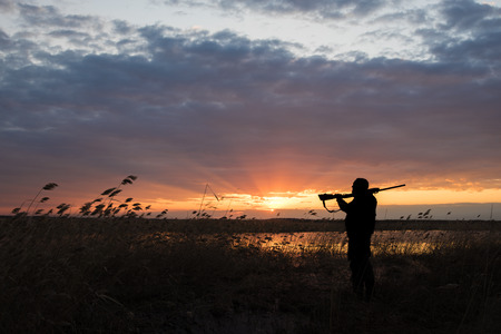A hunter with a gun on a duck hunt