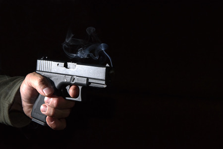 death head holding: Glock pistol in his hand in the dark closeup