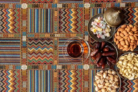 oriental rug: sweets, dates and tea on a traditional Arabian carpet