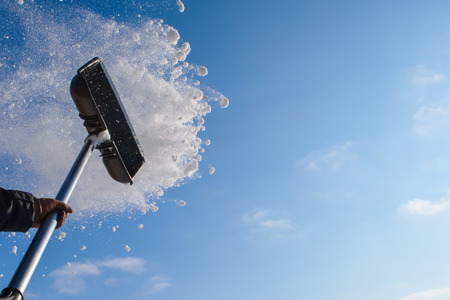Cleaning snow shovel, throwing snow against the sky.
