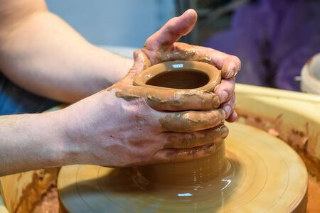 wheel spin: potter makes a pot of clay, working on the potters wheel. Stock Photo