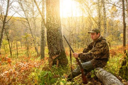 De jager met ruzhom die in het bos op de boomstam van een gevallen boom rust.