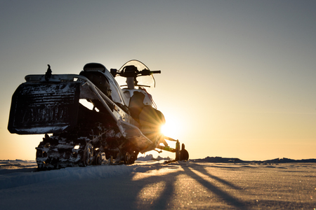 A snowmobile stands on the snow at sunset. Stock Photo
