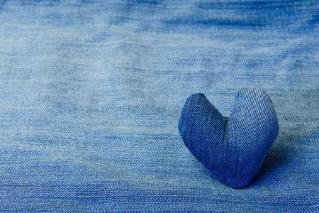 Denim heart lies on a denim background.