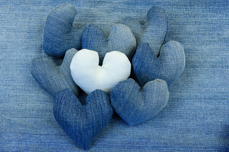 Hearts from denim lie on a denim background. White heart above