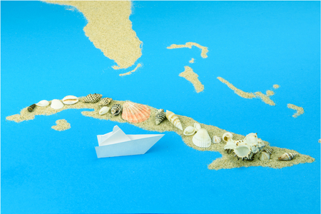 A paper boat sails off the coast of Cuba. The contours of Cuba are lined with sand, on top - shells. Фото со стока
