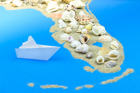 A paper boat stands off the coast of Florida. The contours of Florida lined with sand, on top - shells. Фото со стока