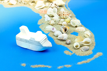 Model cruise liner stands off the coast of Florida. The contours of Florida are lined with sand, on top are seashells. Фото со стока