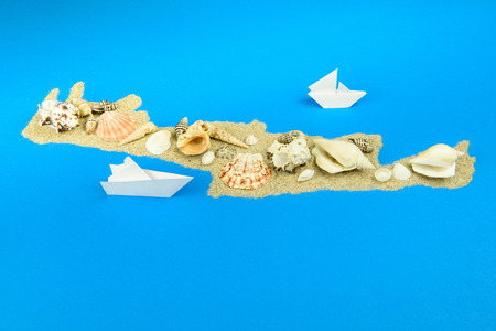 Paper boats off the coast of Crete. The map is lined with sand, with seashells lying on top. Фото со стока