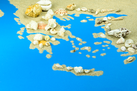 Contours of Greece and islands. The map is made of sand, with seashells on top.