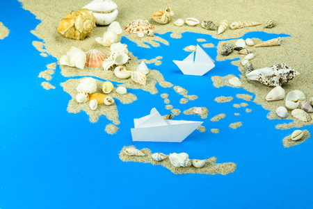 Paper boats off the coast of Greece. The map is lined with sand, with shells on top.