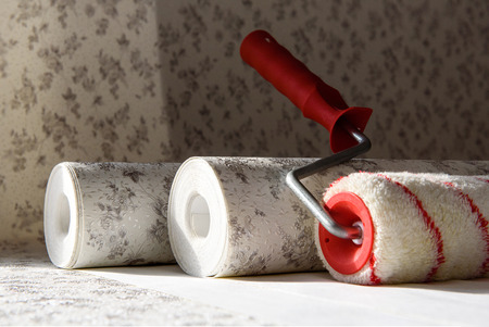 Rolls of wallpaper and roller. Preparation for repair in the apartment.