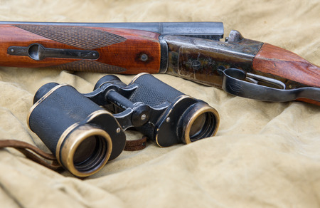 Vintage hunting rifle and binoculars lie on a khaki tent.