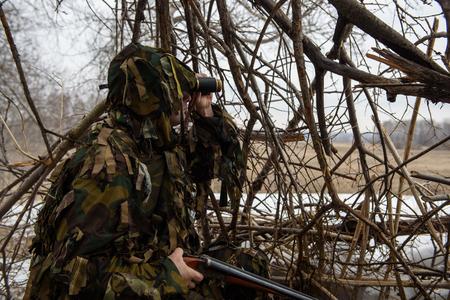 A hunter in binoculars. Aims a gun.