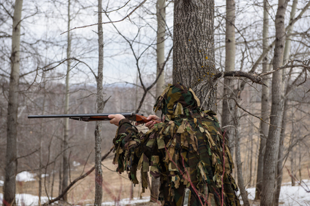 A hunter with a gun sneaks into the forest and looks out for prey. Фото со стока