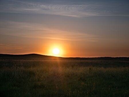Sunset in the Kazakh steppe. Spacious steppes surrounded by low mountains. Beautiful view of horizon.