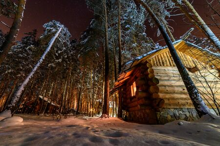 Hut in the woods on a winter Christmas night.