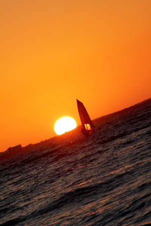 sun going down with wind surfer