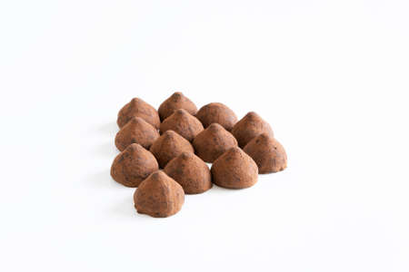 A bunch of sweet chocolate truffles whit chocolate powder on white background.