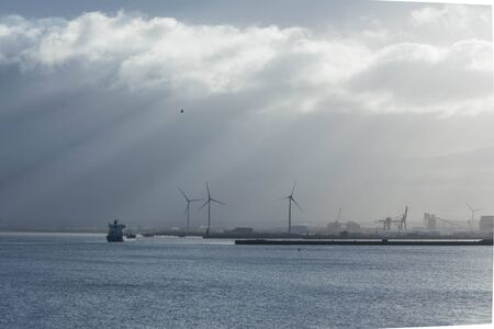 a cargo ship approaches Avonmouth dock with wind turbines in background Banco de Imagens