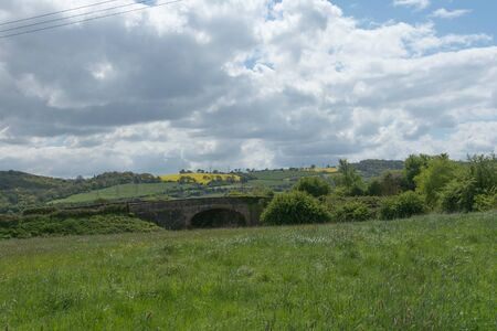 countryside with fields, bridge and rapeseed Фото со стока