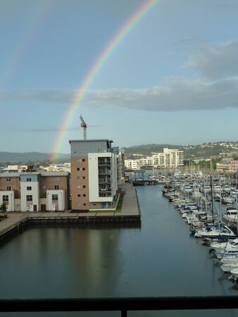 A rainbow arcs over a marina after a storm